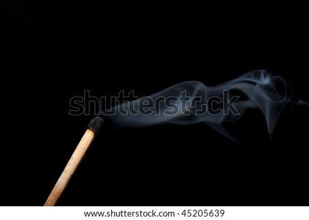 Matchstick and smoke against black background - stock photo