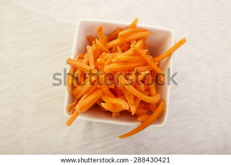 Matchstick sticks of raw carrot in a bowl from above. - stock photo