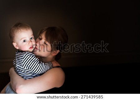Maternal love. Portraits of mother embracing his cute baby son. Image with toning and light effects - stock photo
