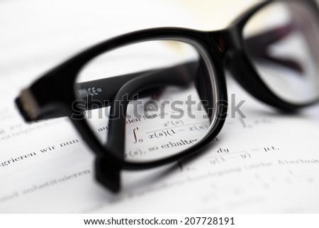 Math book closeup, glasses on top - stock photo