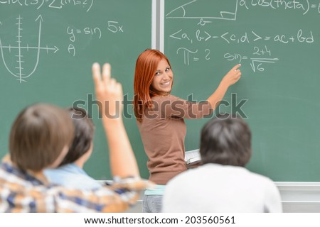 Math lesson student write on green chalkboard looking at classmates
