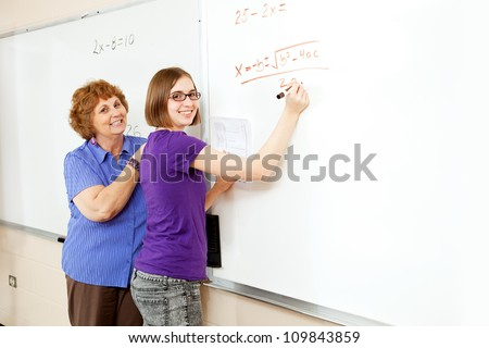 Math student and teacher working problems on the white board, with blank whiteboard space for text. - stock photo
