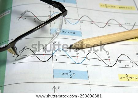 Math study for the exam set (book, pencil, glasses) - Background shows trigonometry formulas - stock photo