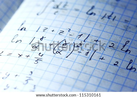 Mathematical equations hand written on paper - stock photo
