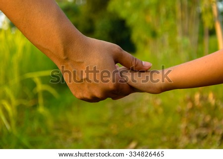 mather giving hand to a child - stock photo