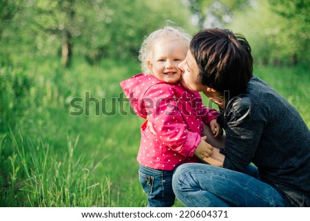 mather kissing her daughter. family outdoor