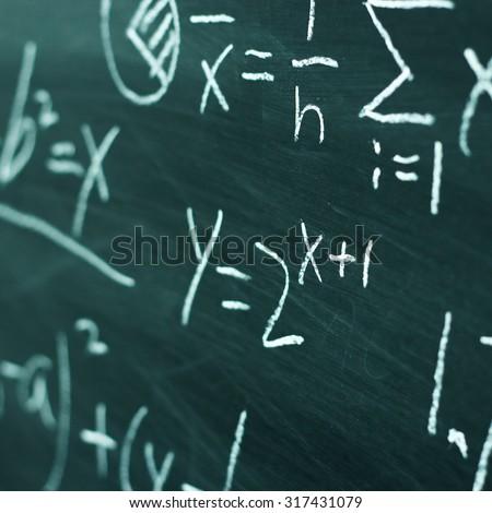 Maths formulas written by white chalk on the chalkboard background. - stock photo