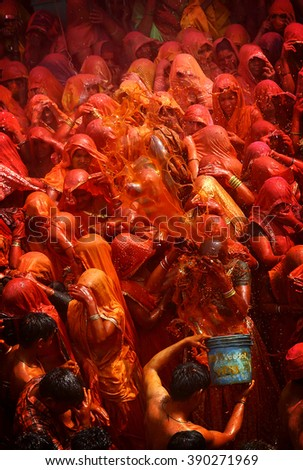 MATHURA,INDIA - 7/03/2015 : Indian devotees dance in colored water at the end of Holi celebrations, the Hindu festival of colors at the Baldev Temple. - stock photo