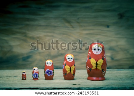 Matryoshka, a Russian wooden doll on wooden table - stock photo