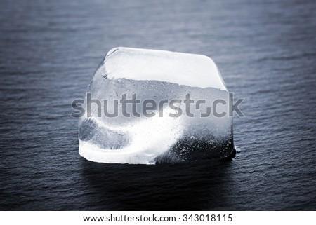 Matted ice cube on dark liquid background - stock photo