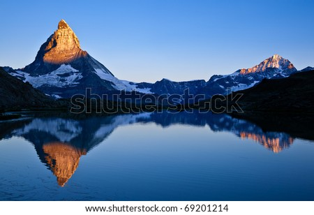 Matterhorn and other peak reflected in the lake - stock photo
