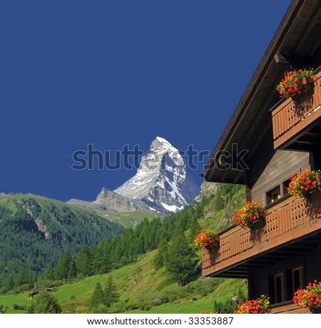 Matterhorn and Swiss chalet - stock photo