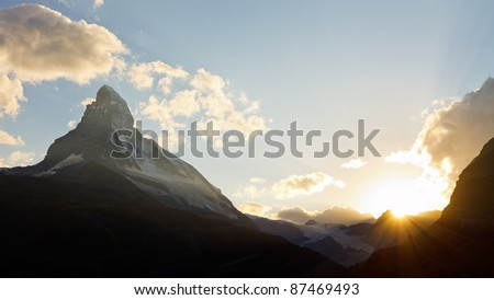 Matterhorn at sunset. The sun is setting behind Switzerland's most iconic mountain. - stock photo