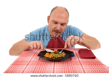 Mature adult eating healthy vegetables with an unhappy face - stock photo