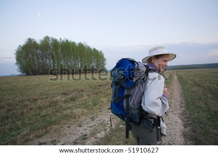 Mature adult woman walking with backpack at field - stock photo