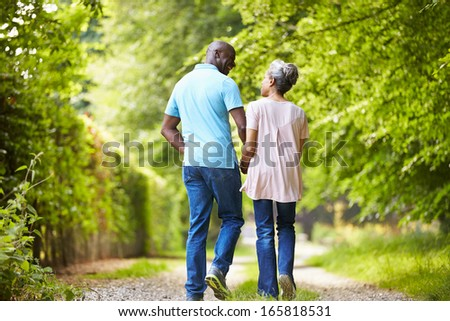 Mature African American Couple Walking In Countryside - stock photo
