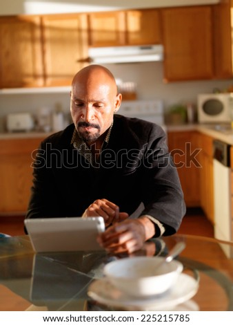 mature african man using tablet before work - stock photo