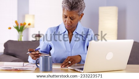 Mature African woman paying her bills - stock photo