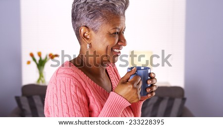 Mature African woman smiling with coffee mug - stock photo