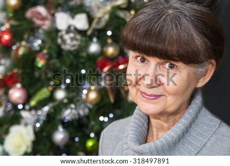 Mature age good looking woman against of Christmas tree. Christmas background - stock photo
