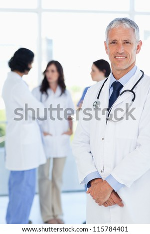 Mature and confident doctor crossing his hands in front of his medical interns - stock photo