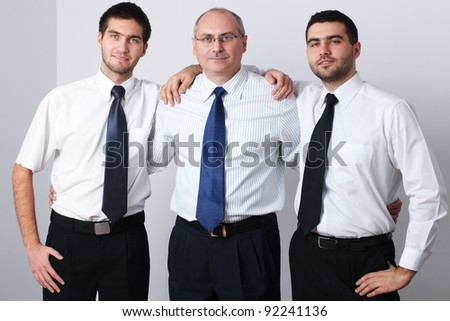 Mature and 2 young businessman celebrate success - stock photo