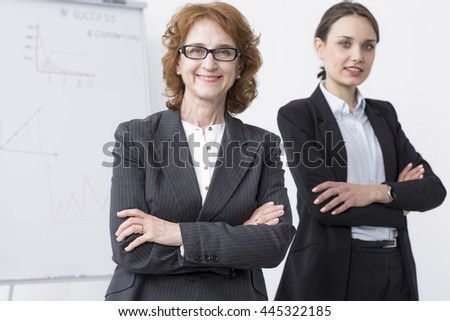 Mature and young businesswomen standing on a light background - stock photo