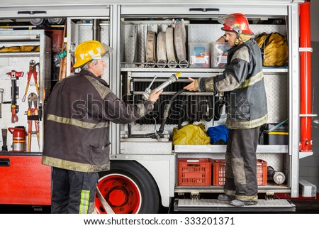 Mature and young firefighters working at truck in fire station - stock photo