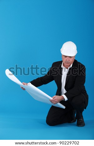 mature architect with blueprints - stock photo