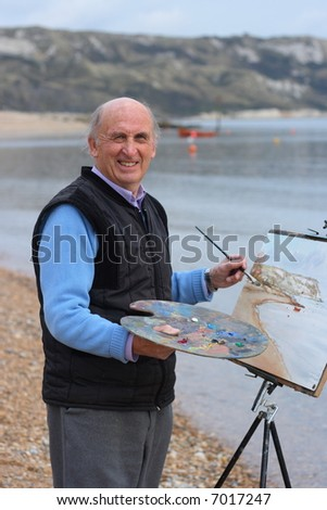 Mature artist painting a coastal landscape with paintbrush, easel and painter's palette. - stock photo