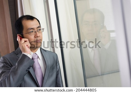 Mature Asian businessman using cellphone in hotel. - stock photo