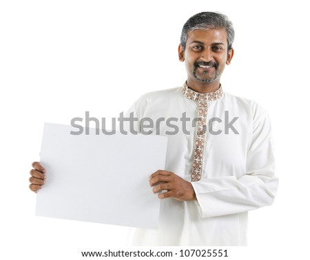 Mature Asian Indian businessman holding a white board standing over white background - stock photo