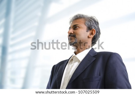Mature Asian Indian businessman looking away standing on office background - stock photo