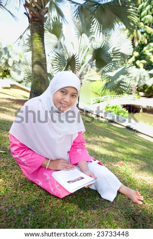 Mature Asian Malay Muslim woman reading, in an outdoor park - stock photo