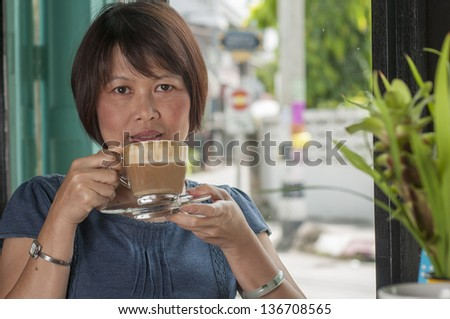 Mature Asian woman drinking coffee - stock photo