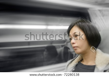 Mature Asian woman in train and looking far away.