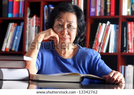 Mature Asian woman reading in the library - stock photo
