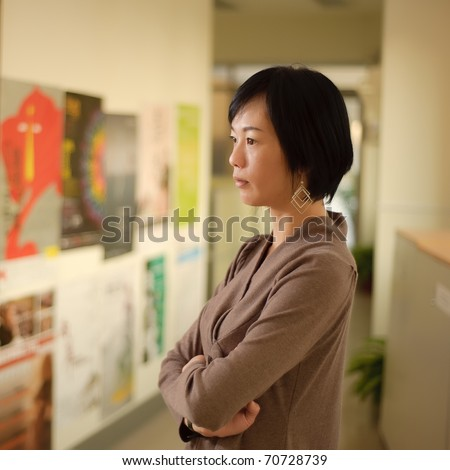 Mature Asian woman thinking, closeup portrait indoor.