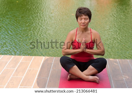 Mature Asian woman with eyes closed sitting in lotus position: healthy lifestyle concept - stock photo