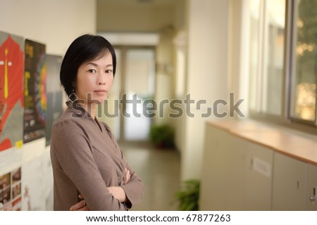 Mature Asian woman with friendly expression and gaze on you.