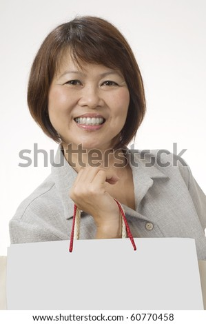 Mature Asian woman with shopping bags isolated on white - stock photo