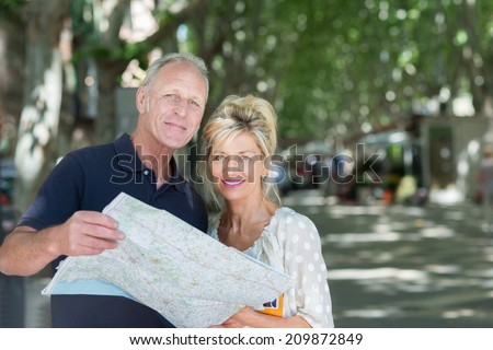 Mature attractive couple on vacation looking at a map as they stand together on a tree lined road looking up at the camera - stock photo