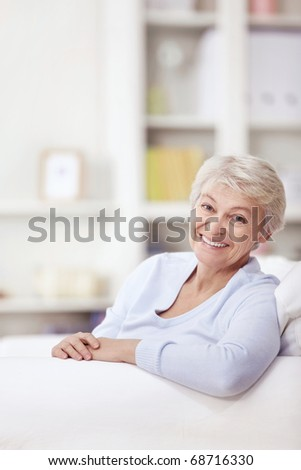 Mature attractive woman on the couch at home - stock photo