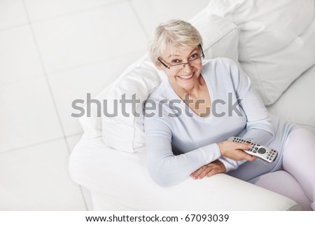 Mature attractive woman with a remote control from a TV on a white sofa - stock photo