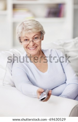Mature attractive woman with a remote control on TV - stock photo