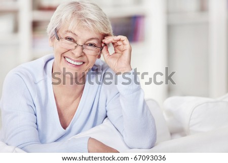 Mature attractive woman with glasses on the sofa - stock photo