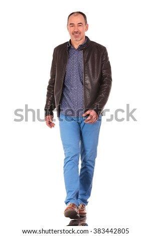mature bald man in leather jacket walking and smiling to the camera in isolated studio background