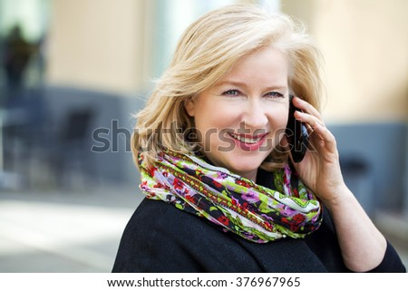 Mature beautiful blonde woman is calling on a cell phone, outdoors in spring - stock photo
