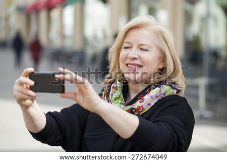 Mature beautiful blonde woman photographed on a cell phone on spring street - stock photo