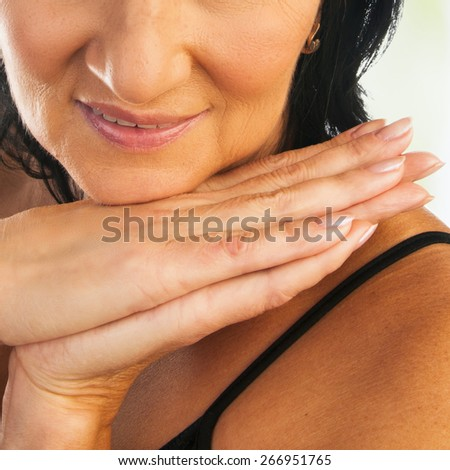 Mature beautiful woman care for her hands - stock photo